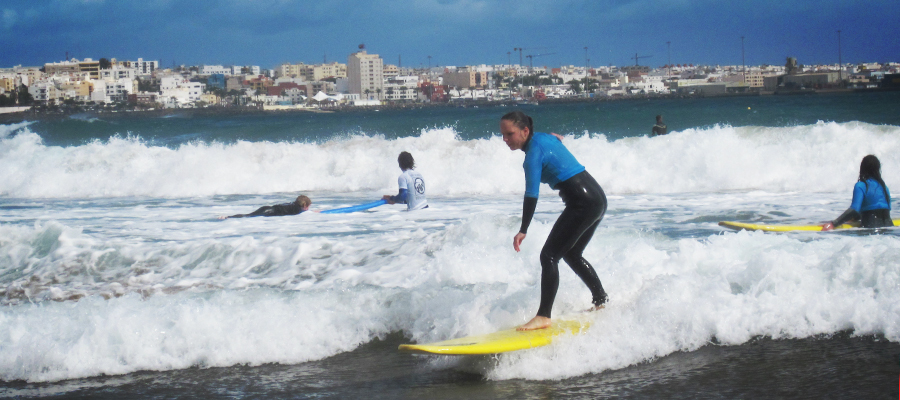 Surf lessons at the Surfcamp Fuerteventura – with Fuerteventura's capital Puerto del Rosario in the background