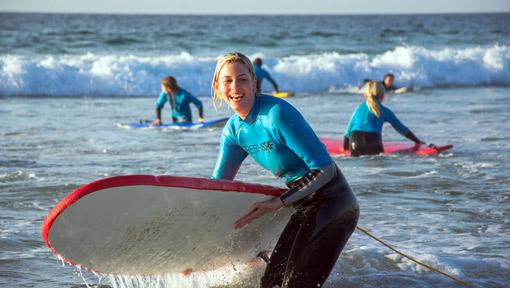 Surfschülerin trägt ihr Surfboard glücklich aus dem Wasser